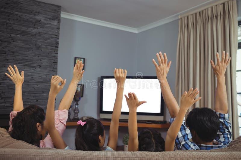 Televisão de observação da família junto na sala de visitas imagem de stock