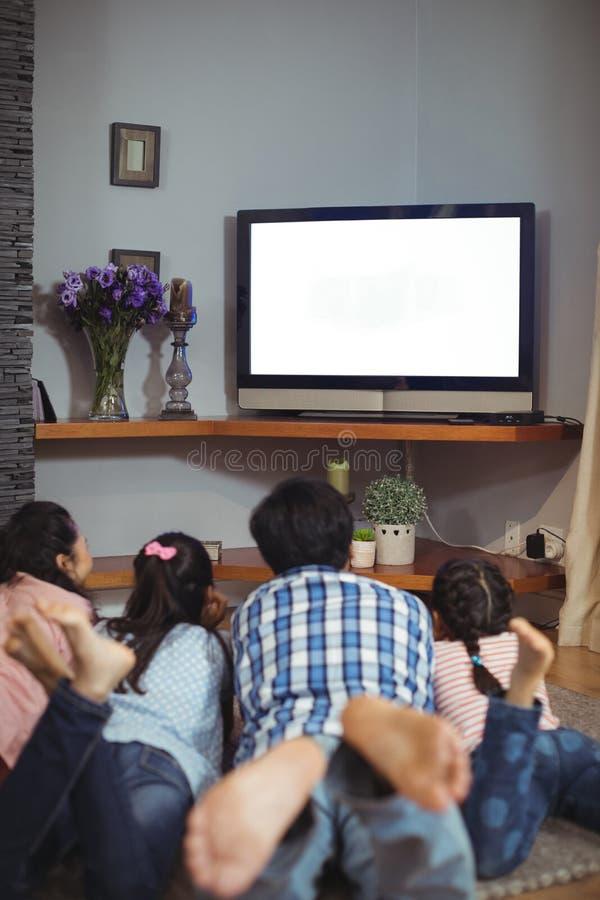 Televisão de observação da família junto na sala de visitas imagens de stock royalty free
