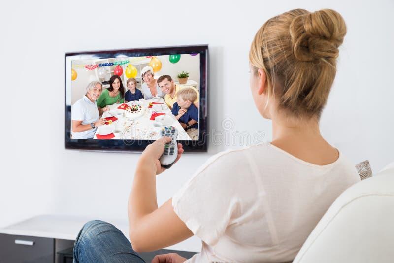Televisão de observação da jovem mulher ao sentar-se no sofá fotografia de stock