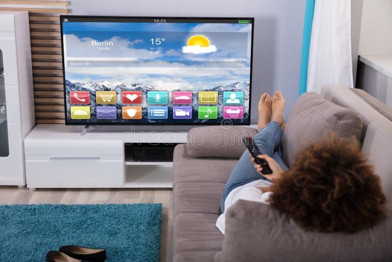 Televisão de observação da mulher com aplicações coloridas na tela fotografia de stock royalty free