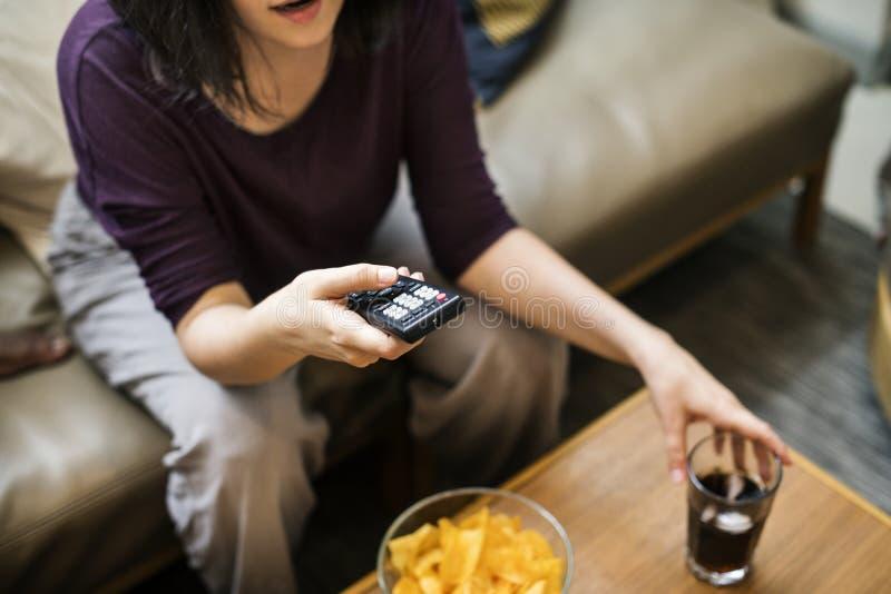 Televisão de observação da mulher no sofá imagens de stock