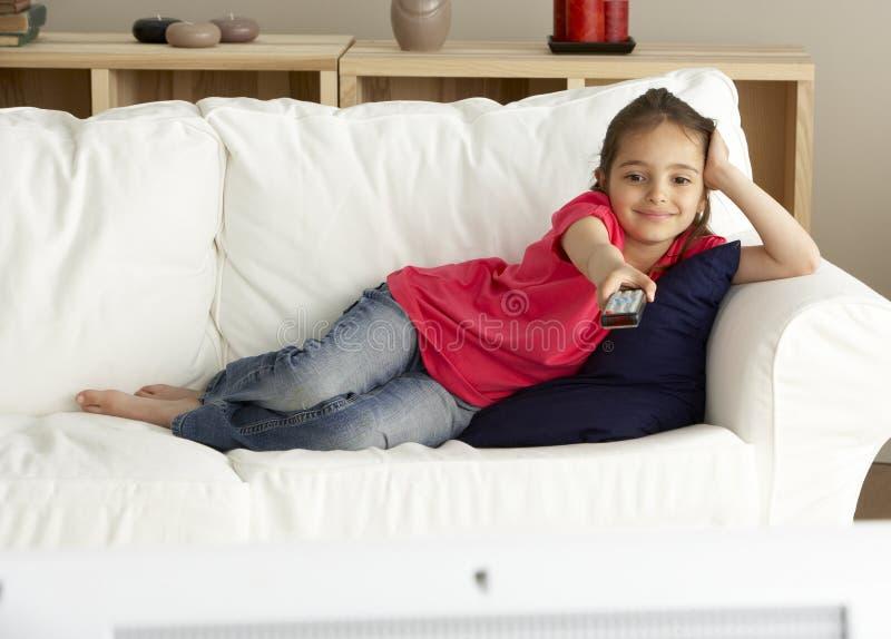 Televisão de observação da rapariga em casa imagem de stock
