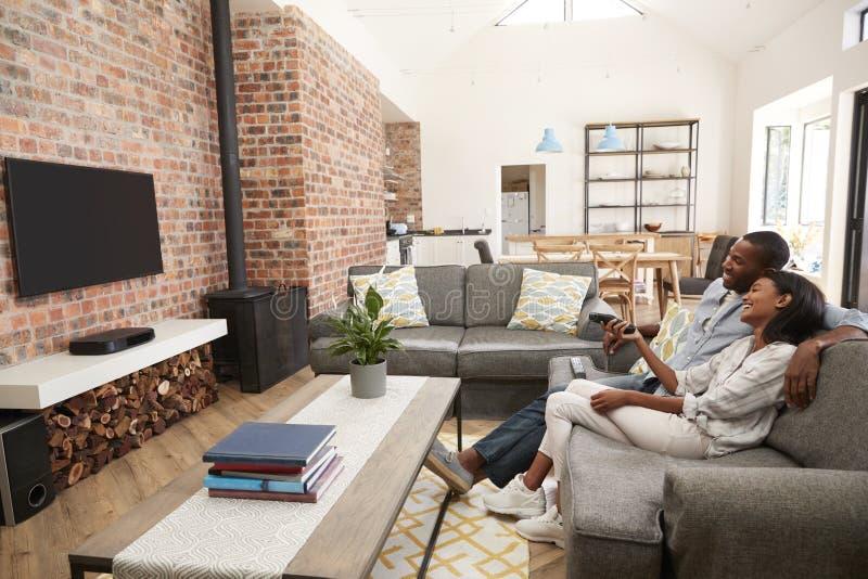 Televisão de observação da sala de estar do plano de Sit On Sofa In Open dos pares fotos de stock