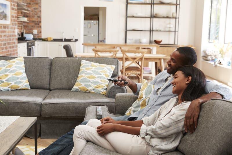 Televisão de observação da sala de estar do plano de Sit On Sofa In Open dos pares fotografia de stock