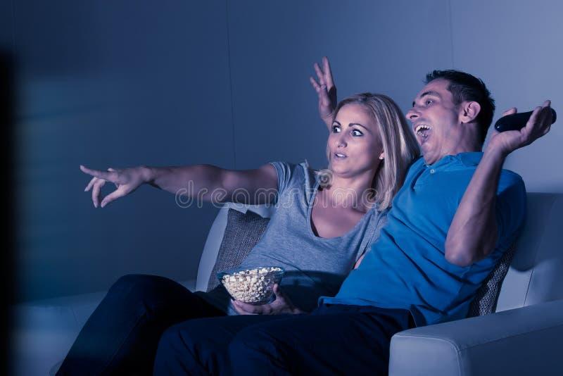 Televisão de observação dos pares assustado fotografia de stock royalty free