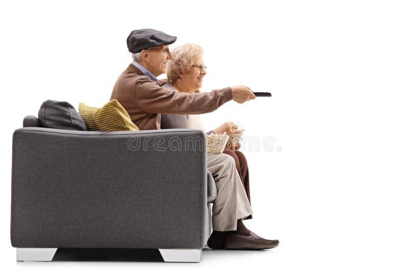 Televisão de observação dos pares idosos com um deles que guardam um re imagem de stock