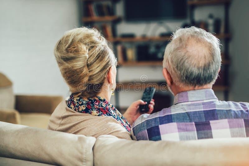 Televisão de observação dos pares idosos que senta-se confortavelmente em um sofá imagens de stock royalty free