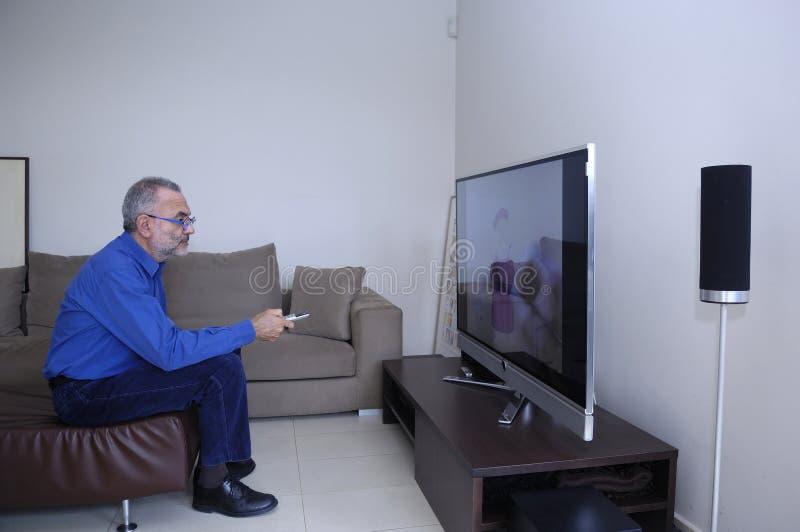 Televisão do homem e controlo a distância de observação da utilização fotos de stock