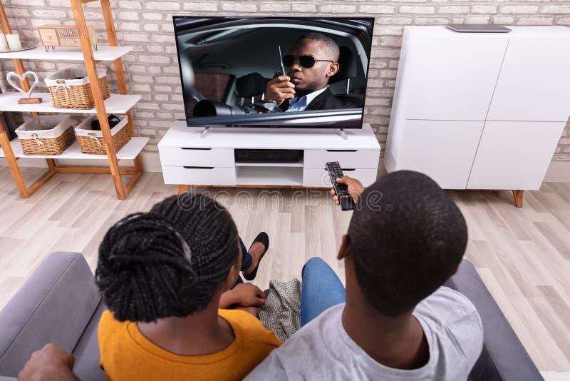 Televis?o de observa??o dos pares africanos felizes fotos de stock royalty free