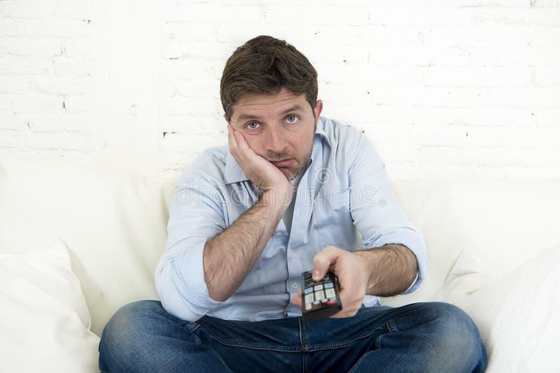Televisión de observación agujereada del hombre que se sienta en el sofá que sostiene teledirigido cansado no divirtiéndose foto de archivo