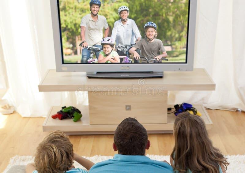 Televisión de observación de la familia en sala de estar imagenes de archivo