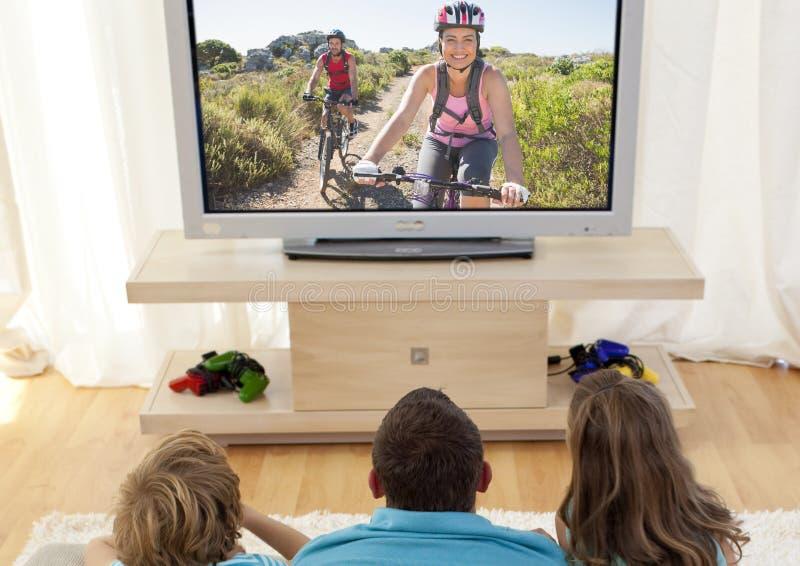 Televisión de observación de la familia en sala de estar foto de archivo libre de regalías