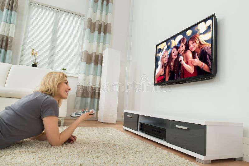 Televisión de observación de la mujer feliz en casa foto de archivo libre de regalías