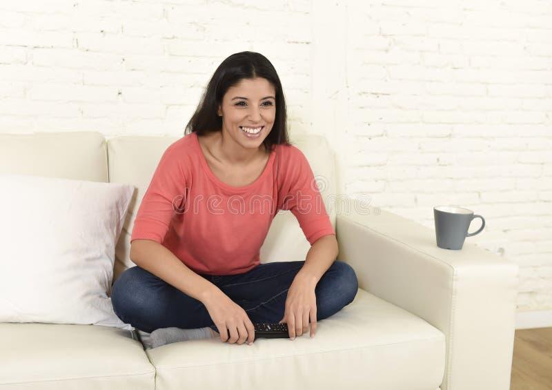 Televisión de observación de la mujer feliz en la película romántica de goce emocionada feliz del sofá del sofá foto de archivo