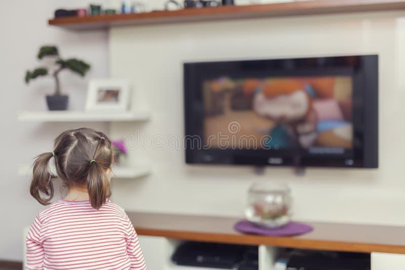 Televisión de observación de la pequeña muchacha linda fotografía de archivo libre de regalías