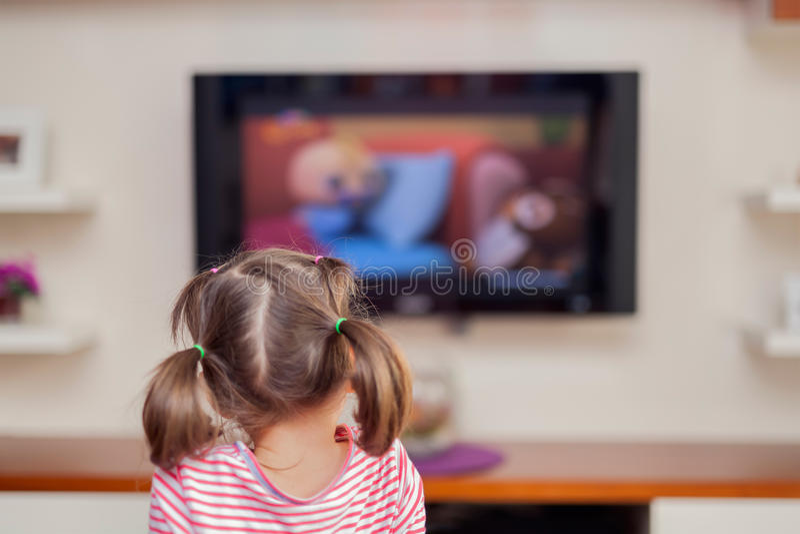 Televisión de observación de la pequeña muchacha linda con la atención imagenes de archivo