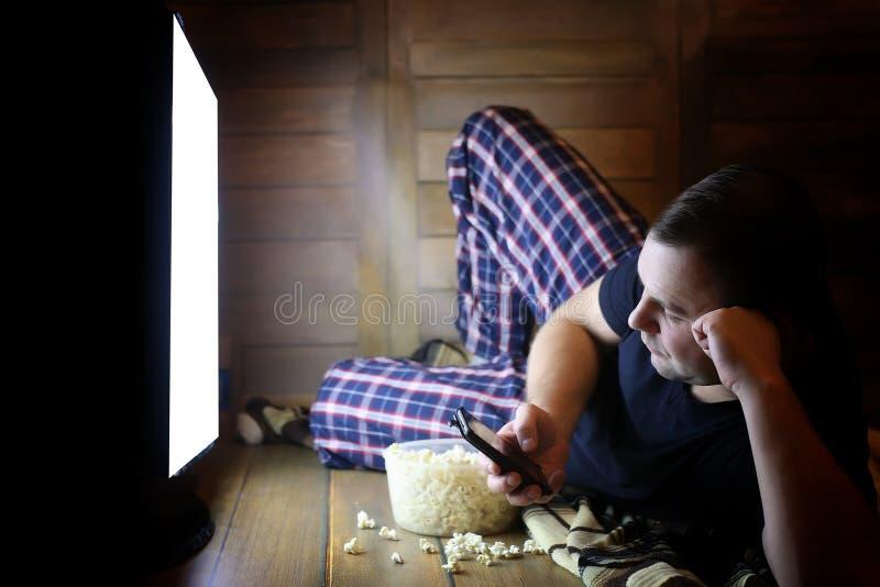 Televisión de observación del hombre joven en casa en el piso imagenes de archivo