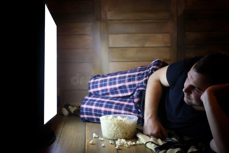 Televisión de observación del hombre joven en casa en el piso foto de archivo libre de regalías