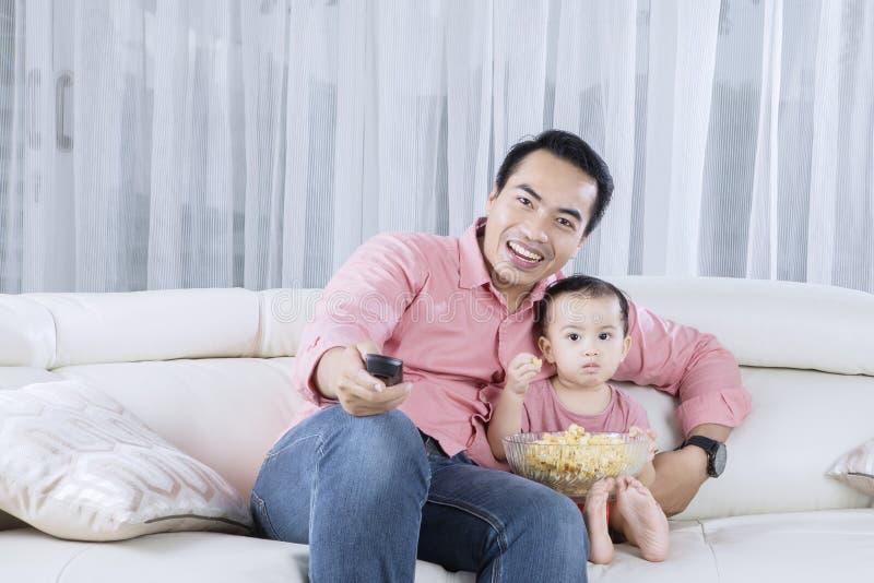 Televisión de observación del padre y del hijo fotos de archivo
