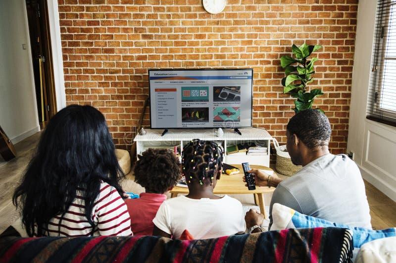 Televisión de observación de la familia africana junto foto de archivo