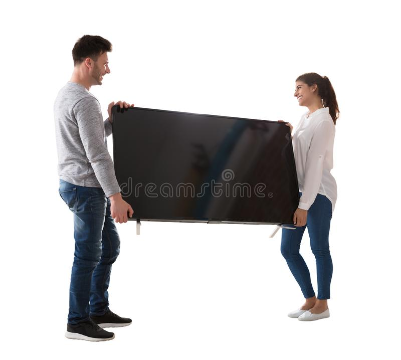 Televisión que lleva de los pares jovenes felices foto de archivo libre de regalías