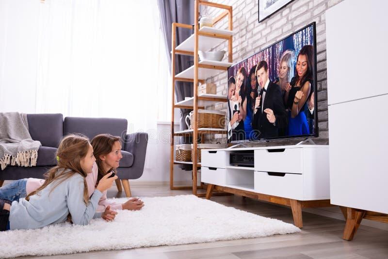 Televisi?n de observaci?n de la madre y de la hija imagen de archivo