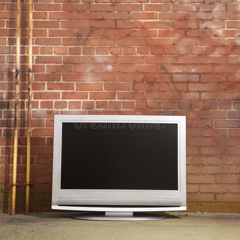 Televisie door bakstenen muur. stock foto