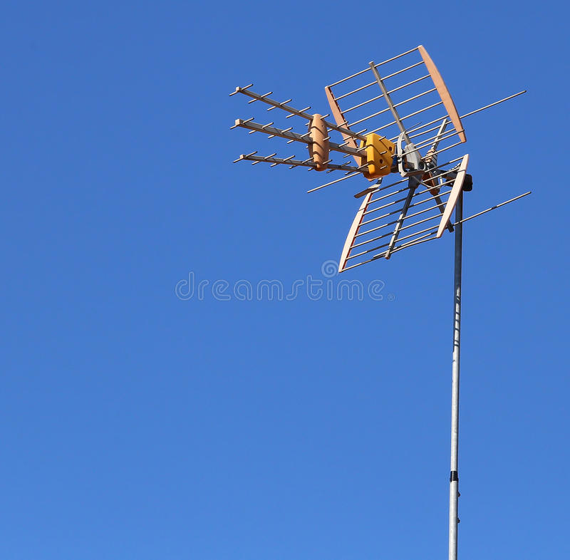 Television antenna to receive television programs. Innovative television antenna to receive television programs and the background of the blue sky royalty free stock photography