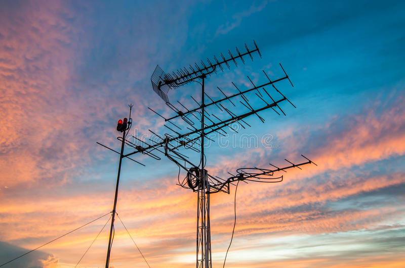 Television antennas. With sunset cloudy sky background stock photos