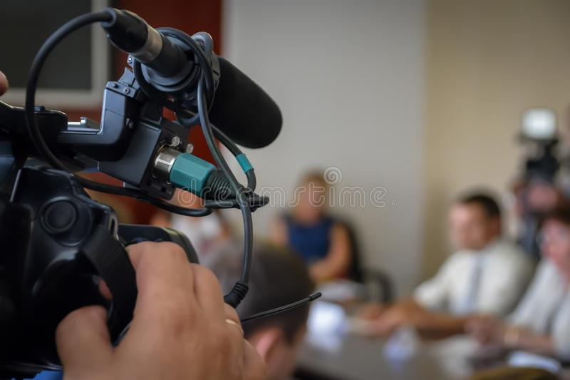 Television Camera Recording News Conference. Spokespersons At The Desk. Journalists Covering A Press Event stock photo
