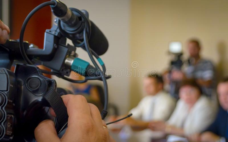 Television Camera Recording News Conference. Spokespersons At The Desk. Journalists Covering A Press Event.  royalty free stock images