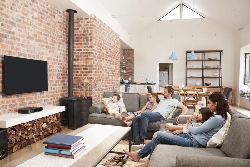Television för vardagsrum för familjSit On Sofa In Open plan hållande ögonen på fotografering för bildbyråer