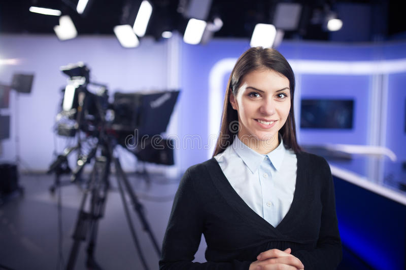 Television presenter recording in news studio. Female journalist anchor presenting business report stock photography