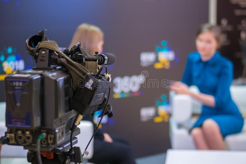 Television video camera recording interview in broadcast news studio royalty free stock image