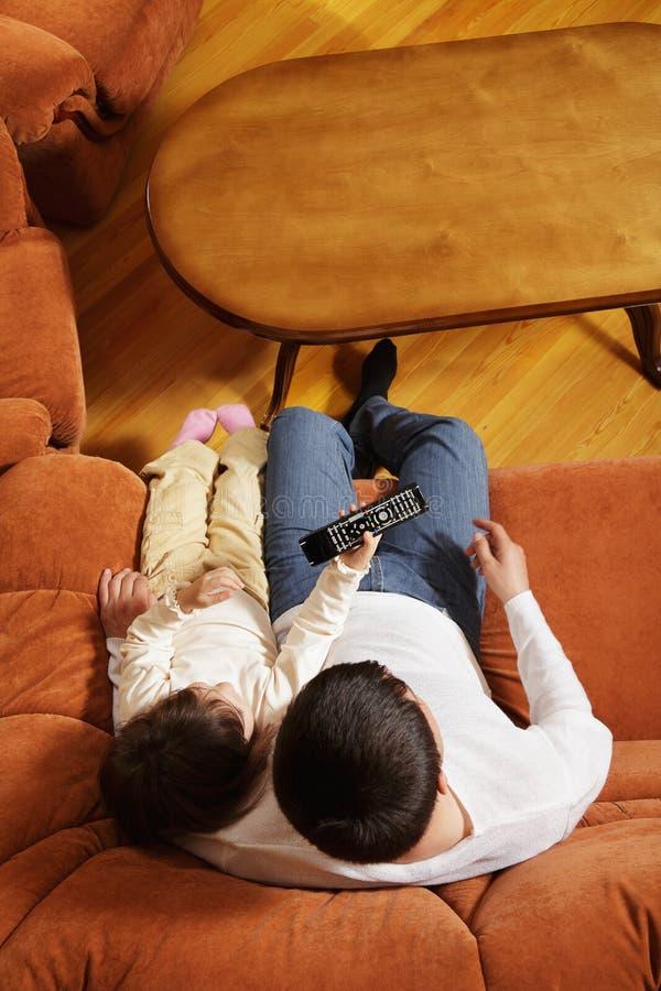 Televisione di sorveglianza del padre con la figlia fotografia stock libera da diritti