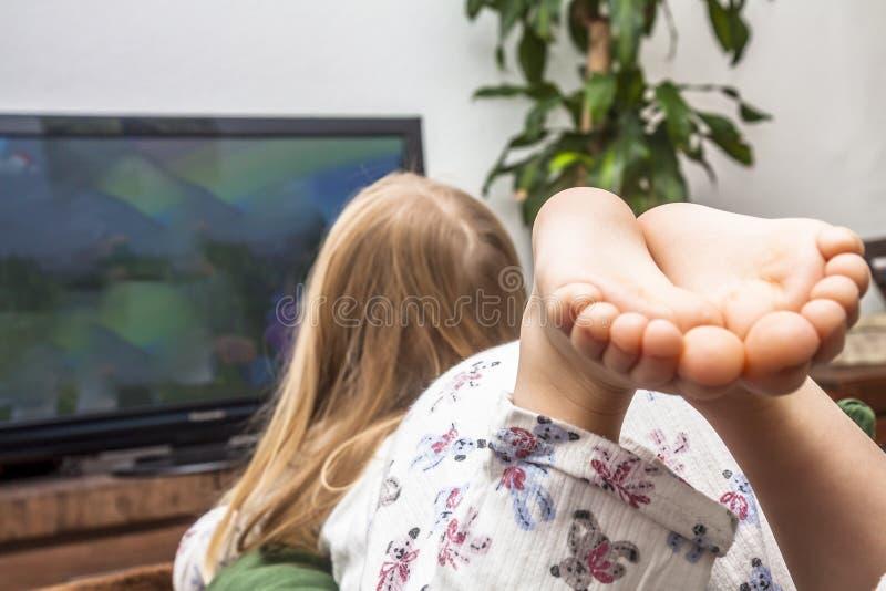 Televisione di sorveglianza della bambina sul sofà immagine stock libera da diritti