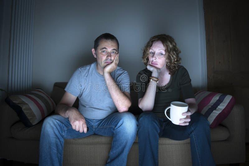 Televisione di sorveglianza delle coppie annoiata fotografie stock libere da diritti