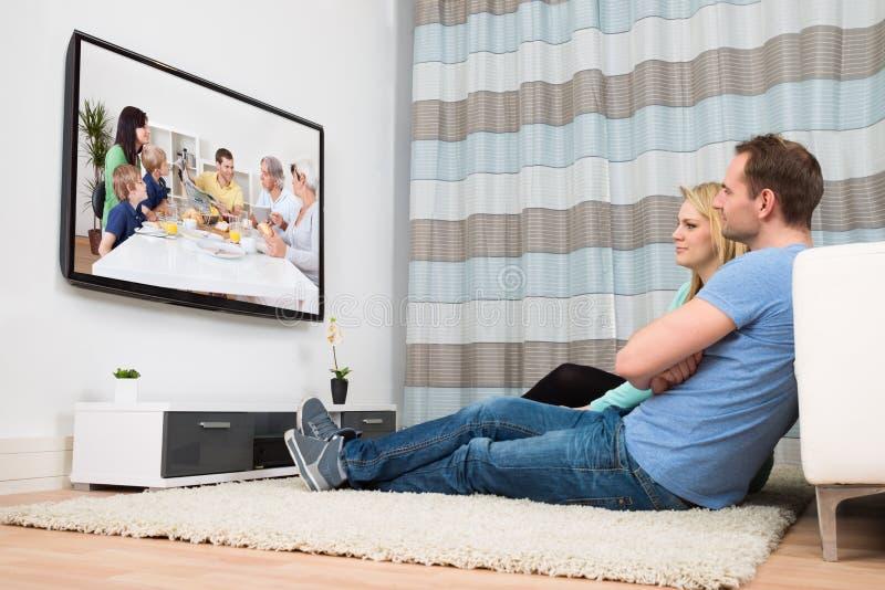 Televisione di sorveglianza delle coppie in salone immagine stock libera da diritti
