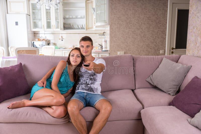 Televisione di sorveglianza delle giovani coppie insieme fotografia stock libera da diritti