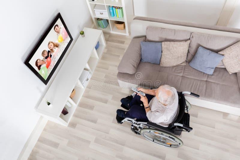 Televisione di sorveglianza handicappata della nonna a casa fotografia stock libera da diritti