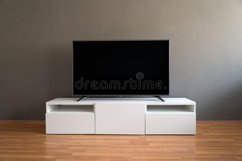 Televisione LCD piana sul gabinetto bianco nel salone immagini stock libere da diritti