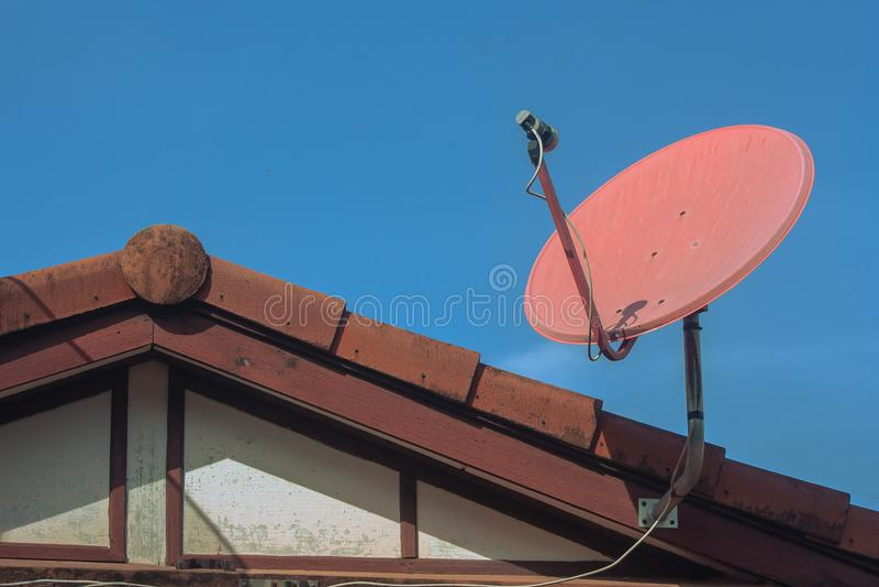 Televisione via satellite di Digital che riceve la regolazione del piatto sopra il tetto della casa con cielo blu nel fondo fotografie stock libere da diritti