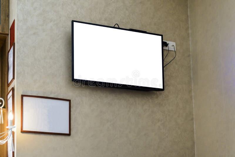 Televisor auf einer Wand mit einem leeren Rahmen für Ihre Werbung stockbild