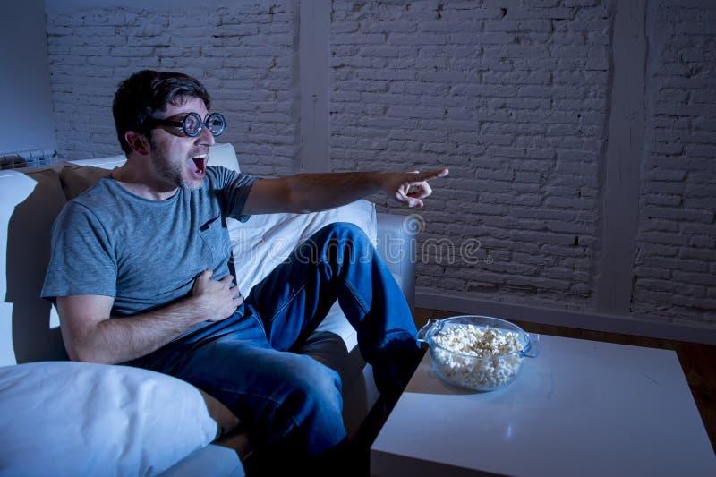 Telewizyjny nałogowa mężczyzna ogląda TV w śmieszny głupek fajtłapy szkieł śmiać się szalony na kanapie zdjęcia stock