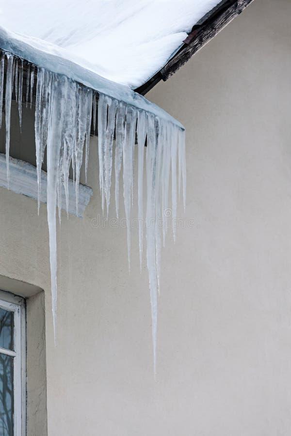 Telhado coberto com a neve e sincelos que penduram para baixo contra a parede imagem de stock