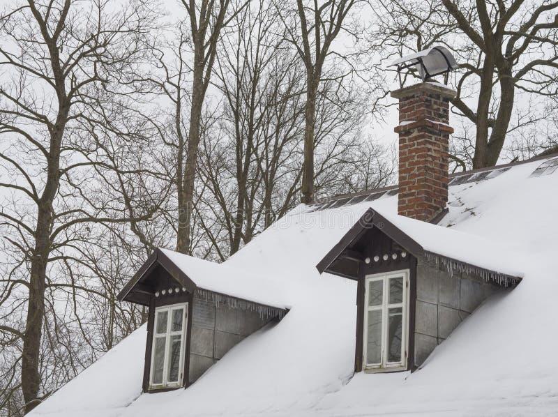 Telhado coberto de neve com chaminé do tijolo e janela de curva da baía com ici fotos de stock royalty free