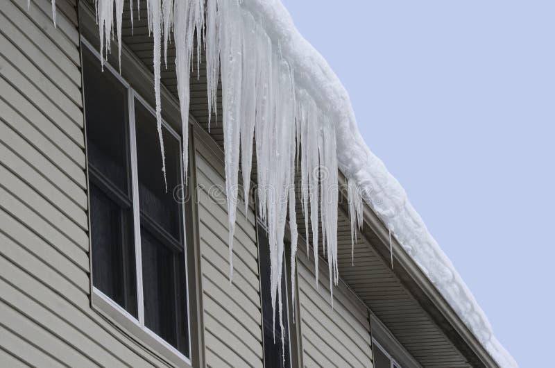 Telhado coberto de neve com os sincelos longos que penduram sobre beirado-através de foto de stock