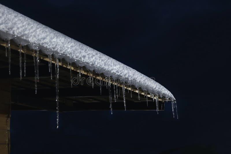 Telhado da casa com neve e sincelos na noite fotografia de stock royalty free
