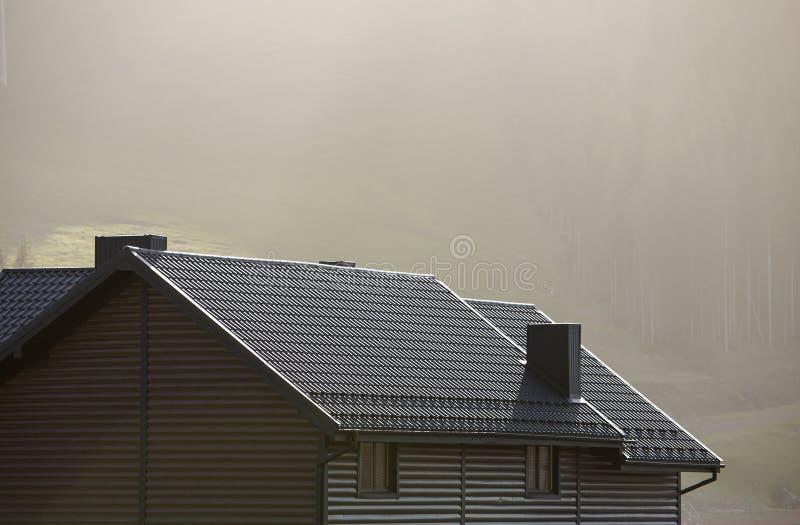 Telhado da casa de campo com paredes de tapume, telhado marrom da telha e chaminés altas na área ecológica no espaço nevoento da  fotografia de stock