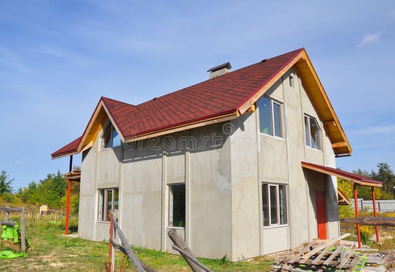 Telhado da casa nova coberto com as telhas do betume Asphalt Shingles Roofing Advantages Construção do telhado e casa da construç imagens de stock
